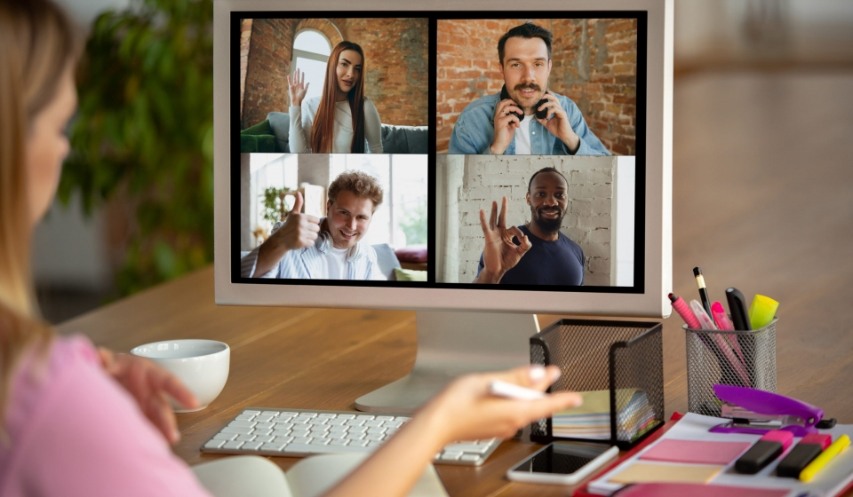 A woman participating in an online meeting with 4 more on-screen participants